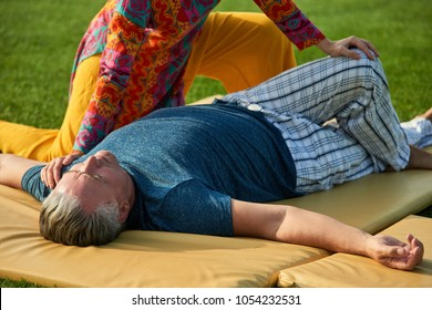 Senior man getting thai massage. Lying on mat, close up.