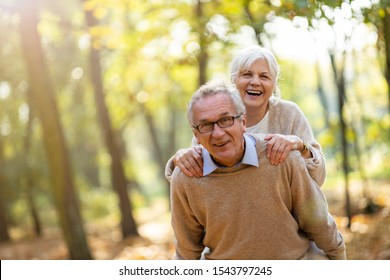 Senior man giving his wife a piggyback outdoors