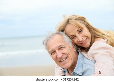 Senior man giving piggyback ride to his wife on the beach
