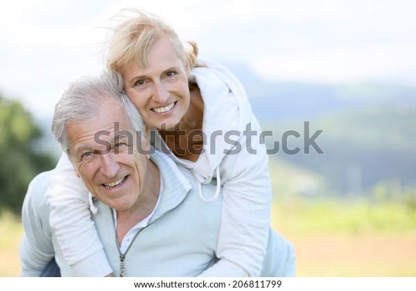 Senior man, der sich mit dem Ferkel zurückfährt