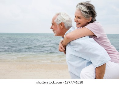 Senior man giving smiling woman piggyback ride on beach vacation