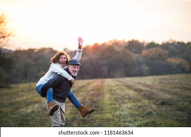 Senior man giving a woman a piggyback ride in an autumn nature.