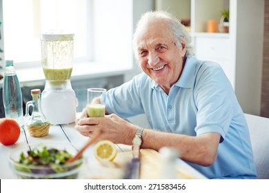 Senior man with glass of fruit smoothie sitting in kitchen