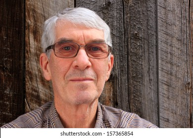 Senior man with glasses and grey hair and a barn wood background.