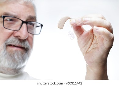 Senior man with glasses holding hearing aid and looking at it.