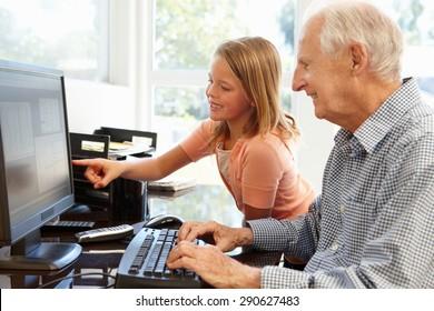 Senior man and granddaughter using computer