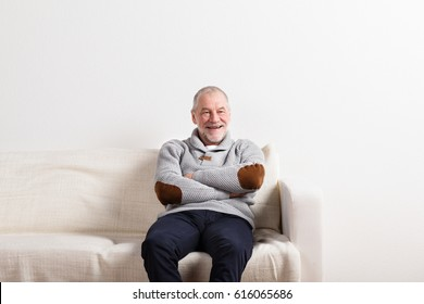 Senior man in gray sweater sitting on sofa, studio shot.