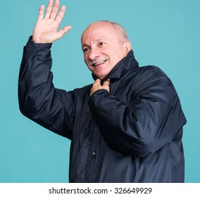 Senior man greeting someone on a blue background