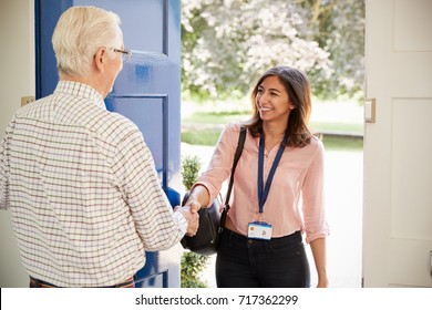 Senior man greeting young woman making home visit