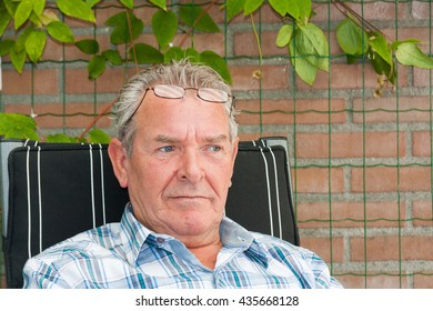 Senior man with grey hair sitting outside in deeps thoughts with reading glasses on his forehead