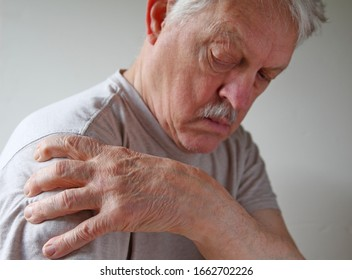 Senior man grips his shoulder in pain with room for text
