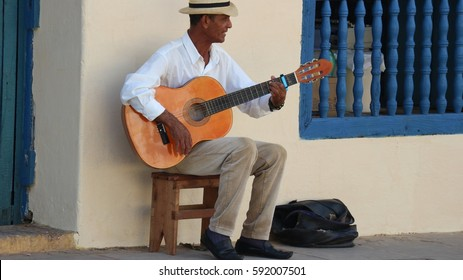 Senior man with guitar wearing a traditional panama straw hat busking in a street in Trinidad, Cuba