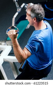Senior man in the gym lifting weights on a lat pull machine, exercising