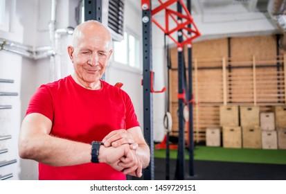 Senior man at the gym using smartwatch