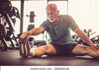 Senior man at gym working exercise and stretching on floor..