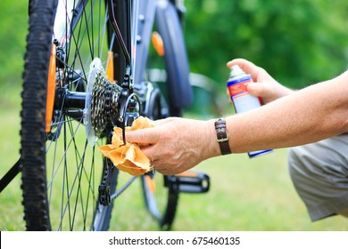 Senior man hands spraying an oil to chain from the wheel bike, doing maintenance
