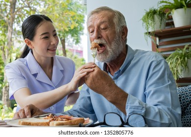 senior man happiness with smiling nurse, takes care breakfast at balcony near garden at nursing home