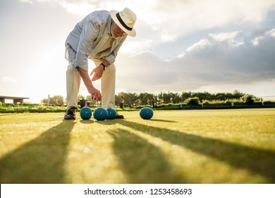 Senior man in hat bending down to pick a boules standing in a playground. Elderly man playing boules in a lawn with sun in the background.