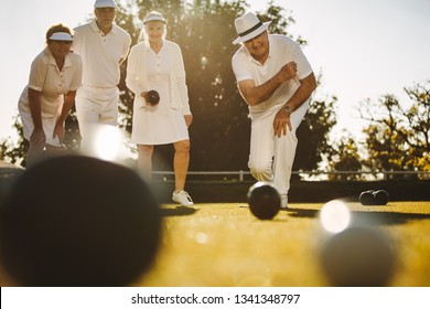 Senior man in hat bending forward to throw a boules in a lawn. Elderly man playing boules in a lawn with his friends.