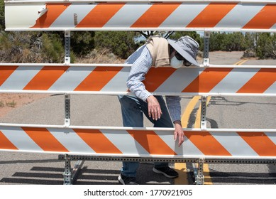 Senior man in a hat and mask behind a road barrier