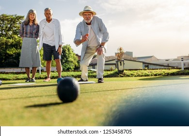 Senior man in hat throwing a boules while his friends look on. Two old men and a woman playing a game of boules in a lawn on a sunny day.