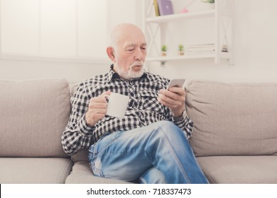 Senior man have rest using smartphone while drinking coffee or tea, sitting on sofa at home, copy space
