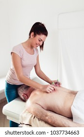 Senior man having chiropractic back adjustment. Pain relief concept, physiotherapy.