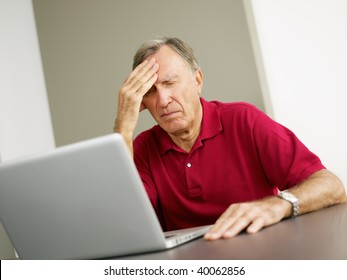 Senior man having headache while using laptop. Copy space