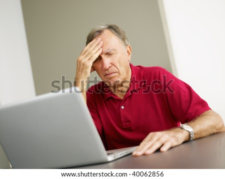 Senior man having headache while using laptop. Copy space