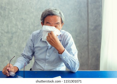 Senior Man Having Influenza Sickness While Using Tissue Paper Wiping Blowing His Nose, Close-Up of Elderly Male Having Ill and Sneezing Form Flu Virus. Senior Asian Man Unwell Symptoms, Health care