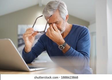 Senior-Mann mit MigGraGrau während der Arbeit am Notebook-Computer