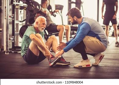 Senior man having sports injury. Personal trainer giving help.