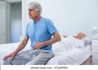 Senior man having stomach pain while sitting on bed at home