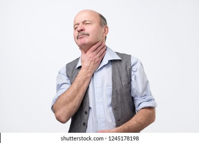 Senior man having terrible pain in throat. Pharyngitis or cancer symptom