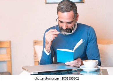 Senior man having troubles reading a book with his glasses, coffee shop surrounding