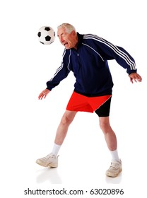 A senior man heading a soccer ball.  Isolated on white.