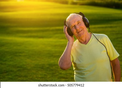 Senior man in headphones. Smiling person on nature background. My favorite song. The quality of sound.
