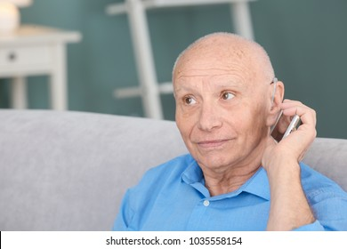 Senior man with hearing aid talking on phone indoors