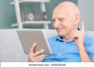 Senior man with hearing aid using tablet computer indoors