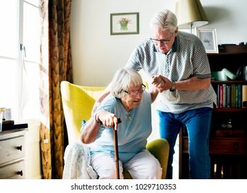 Senior man helping senior woman to stand