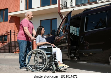 Senior man helping young woman in wheelchair to get into van outdoors