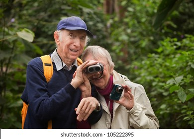 Senior man helps wife look through binoculars in forest