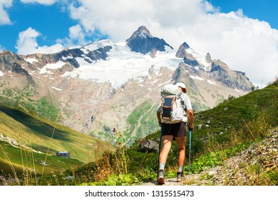 Senior man hiking French Alps in summer with solar backpack. The Aiguille des Glaciers, mountain in the Mont Blanc massif. View From Chapieux valley, Savoie, France.