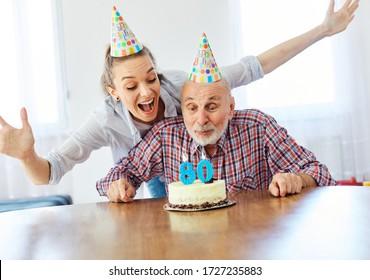 Senior man and his daughter celebrating his 80th birthday at home