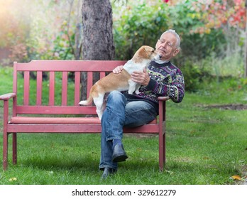 Senior man with his dog sitting on bench in the park