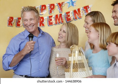 Senior man in his honor giving speech at retirement party with arms around wife by family