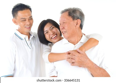 Senior man with his son and daughter. Happy Asian family senior father and adults offspring having fun time at indoor studio.