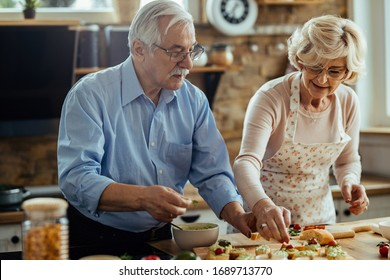 Senior man and his wife enjoying in preparing food in their kitchen.