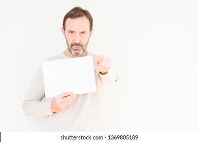 Senior man holding blank paper sheet over isolated background pointing with finger to the camera and to you, hand sign, positive and confident gesture from the front