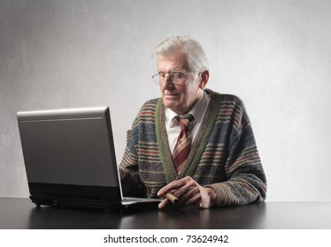 Senior man holding a cigar while using a laptop